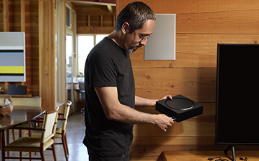 A SONOS in-wall speaker can be seen in the background where a man is holding a Sonos Amp.ng a