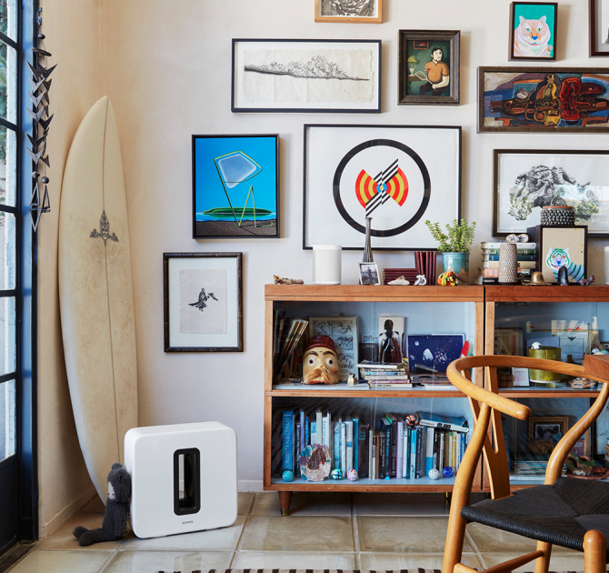 SONOS Sub in white on the floor in front of a surf board, a wall with lots of framed pictures and a cluttered shelving unit.