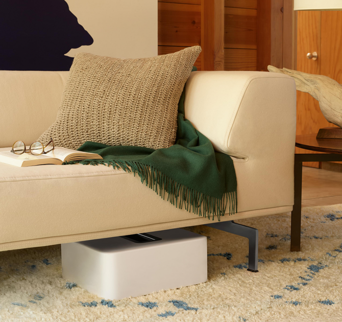 SONOS Sub in white laying down under a sofa that has an open book and a pair of glasses laying on it.