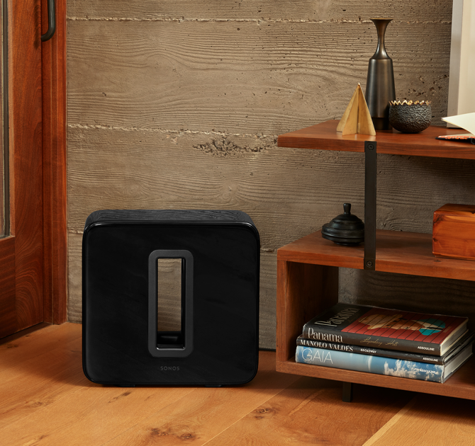 SONOS Sub in black next to a set of floor standing shelves