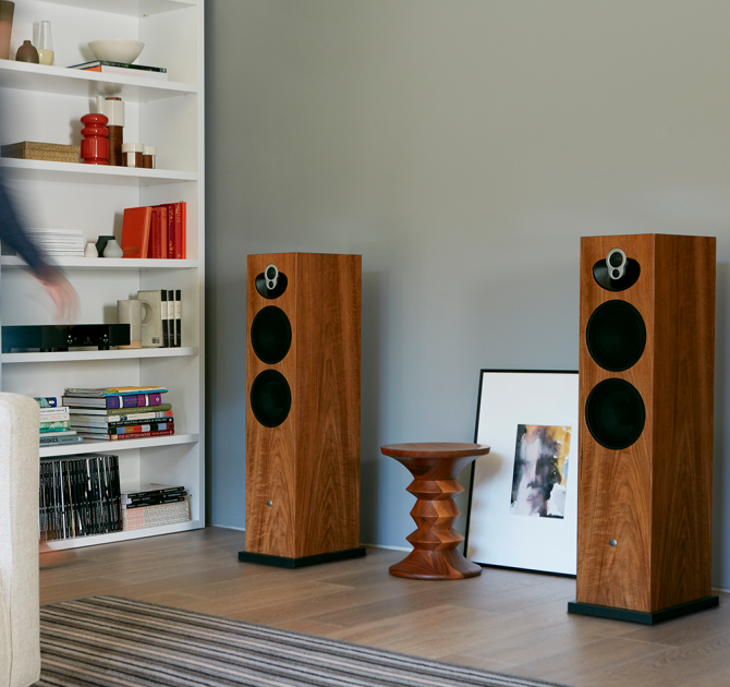 a pair Linn Majik 140 Loud Speakers with a table between them and a set of shelves to the side.