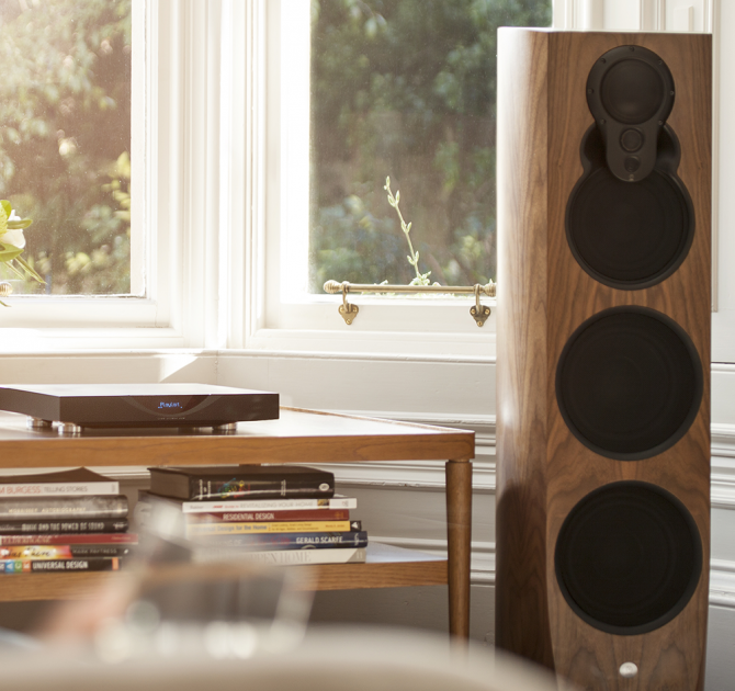 Linn Klimax 350 Exakt Loud Speakers Aktiv in front of a window and next to a coffee table piled with books.