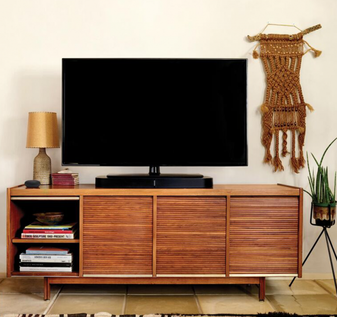 SONOS Playbase Black on top of a wooden sideboard with a television standing on it.