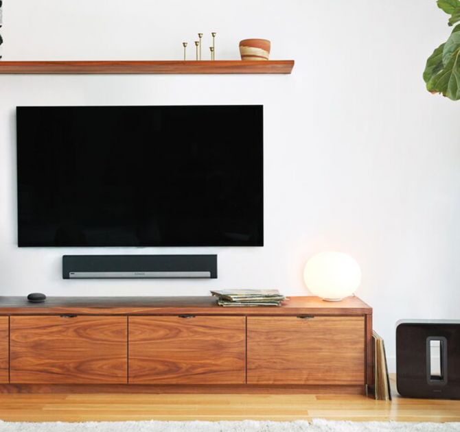 SONOS Playbar wall mounted underneath a television on a white wall above a long, low wooden cabinet.
