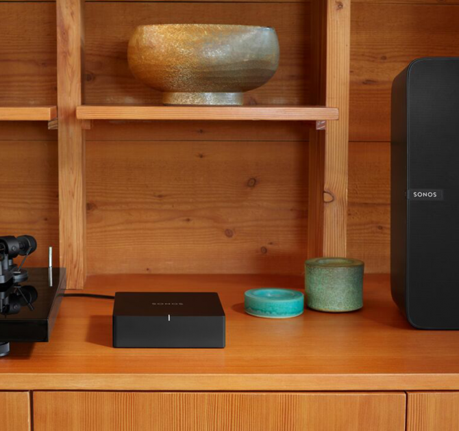 SONOS Port on a wooden sideboard with a bowl on a shelf above it and a SONOS Play:5 to the right.