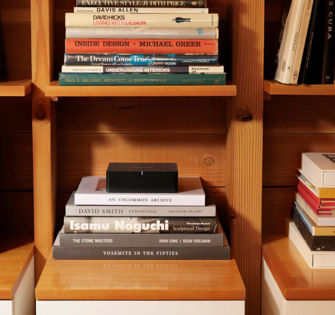 SONOS Port in a wooden modular shelving unit on top of a stack of books.