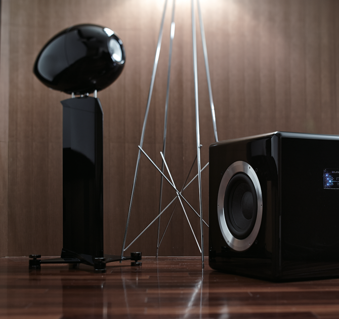 Eclipse TD725SWMK2 Subwoofer on a wooden floor with an Eclipse speaker.