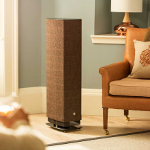 Linn Series 5 530 Exakt Active Speaker in Harris Tweed beside a chair in a well lit living room.  There's a large lamp in the background.