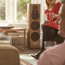 Linn Klimax 350 Exakt Loud Speakers Aktiv in front of a window, next to a coffee table piled with books.  A lady sits to the right of the speaker with a glass of wine in her hand.