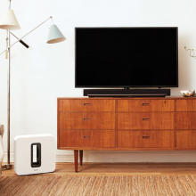 SONOS Playbar sitting on a wooden sideboard with a television behind it.