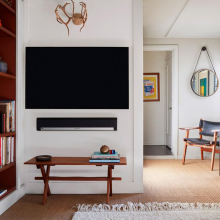 SONOS Playbar wall mounted underneath a television with a small table below.