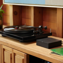SONOS Port on a wooden unit with a record player to the left of it.