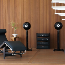 Eclipse TD712zMK2 Speaker on Stand (Single) in black with a hifi system on shelving and a chair for lounging on.