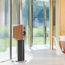 A single Titan 505 speaker on a stand with the grill off in front of large glass doors.