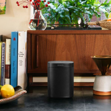 Sonos One Black next to a bowl with a lemon in with a wooden sideboard behind it with cookery books stood up to the left and a vase on top with stems of red berries in.